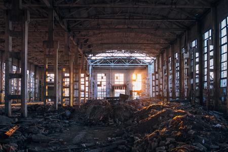 La luz del sol del atardecer en el gran edificio industrial abandonado de la fábrica de excavadoras Voronezh. Foto de archivo