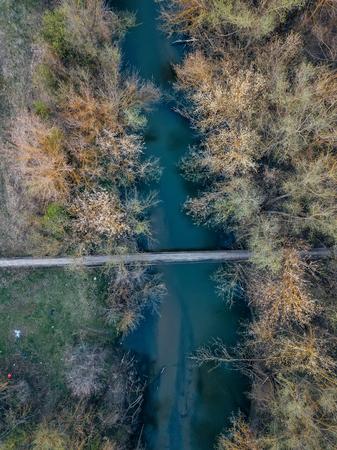 Pedestrian suspension bridge across small river, top view.