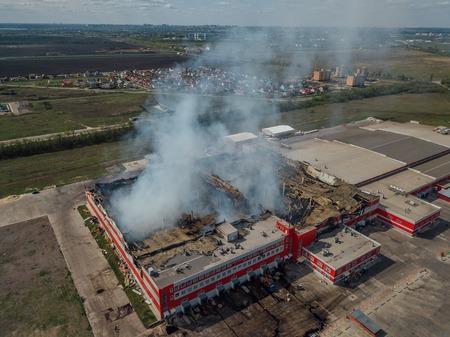 Almacén de distribución industrial en llamas, vista aérea de drones Foto de archivo