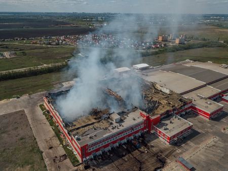 Burning industrial distribution warehouse, aerial drone view