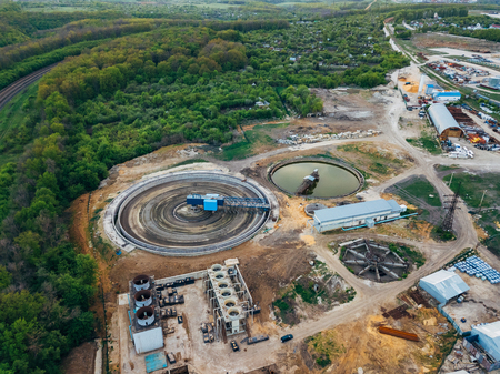 Round clarifiers at wastewater treatment plant, aerial view from drone. Stock Photo