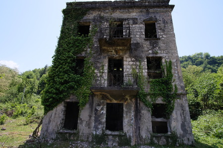 Ruined overgrown apartment house in ghost mining town, consequences of war in Abkhazia, green post-apocalyptic concept Stock Photo