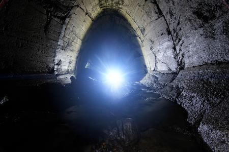 Underground river flowing through large oviform underground sewer tunnel