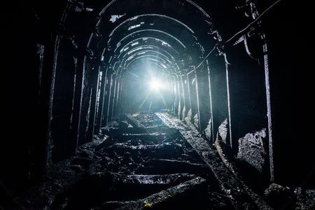 Dark abandoned coal mine with rusty lining in backlight Stock Photo