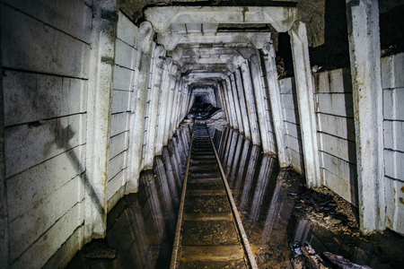 Flooded abandoned uranium mine with rusty railway
