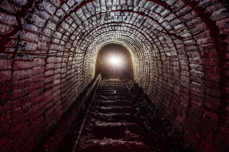 Dark dirty abandoned uranium mine with rusty remnants of railway Banco de Imagens