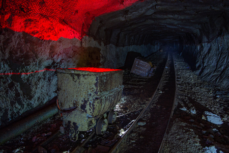 Dirty abandoned uranium mine with rusty rail and trolley