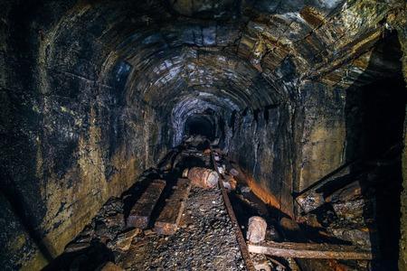 Dark abandoned coal mine with rusty remnants of equipment Imagens