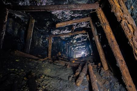 Miniera di carbone abbandonata con supporti di minatori di legno crollati marci. Vecchio sviluppo di carbone abbandonati.