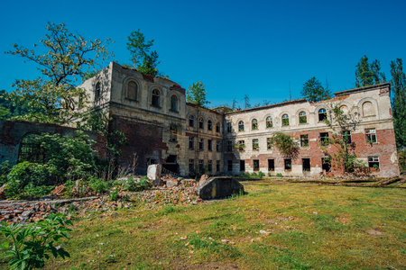 Ruined overgrown school in ghost mining town Akarmara, consequences of war in Abkhazia, green post-apocalyptic concept