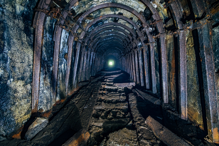Dark abandoned coal mine with rusty miner stands
