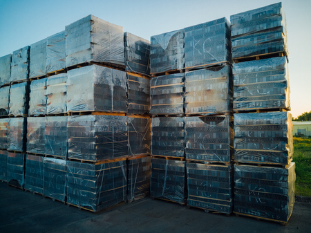 Stack of gray bricks packs on new construction site. Imagens