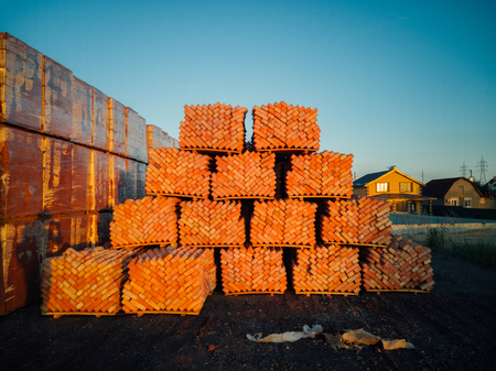 Stack of orange bricks packs on new construction site.