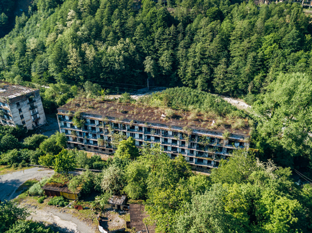 Ruined overgrown apartment house in ghost mining town, consequences of war in Abkhazia, aerial view from drone.