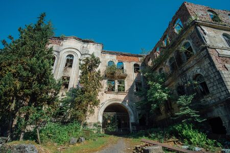 Ruined overgrown hospital in ghost mining town Akarmara, consequences of war in Abkhazia, green post-apocalyptic concept. Imagens