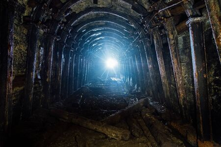 Dark abandoned coal mine with rusty lining in backlight.
