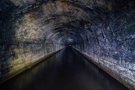 Dark flooded concrete vaulted drainage mine tunnel.