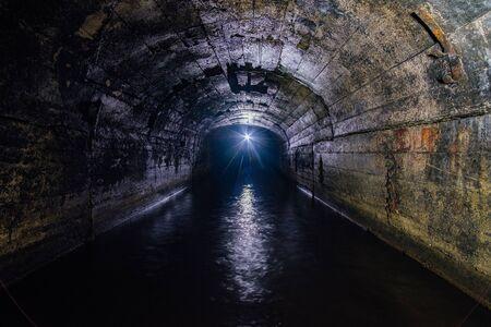 Túnel de la mina de drenaje abovedado de hormigón inundado oscuro. Foto de archivo