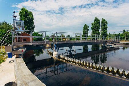 Modern urban sewage treatment plant. Sedimentation drainages round form.