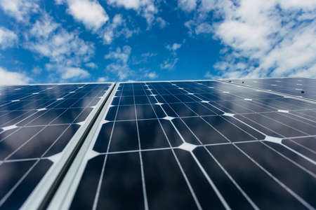 Solar panels on blue cloudy sky background