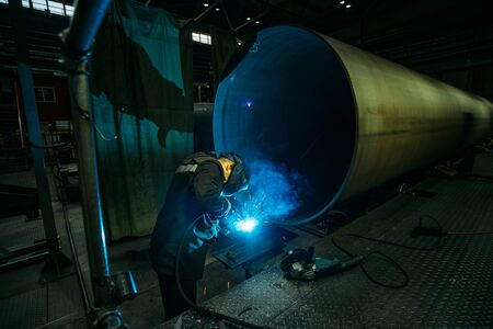 Worker in protective mask welding pipe in factory.