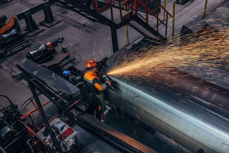Worker cleans welded seam on steel pipe using grinding machine in metalwork workshop. 写真素材