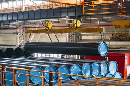 Polymer coated pipe transportation by overhead crane in warehouse.