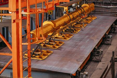 Overhead crane with vacuum handling grippers lifting iron sheets. Stockfoto