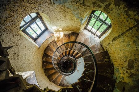 Old spiral staircase in abandoned mansion, upside view.