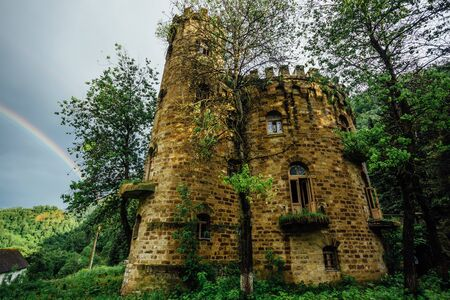 Old abandoned mansion in Gothic style in Caucasian mountains. Stock Photo