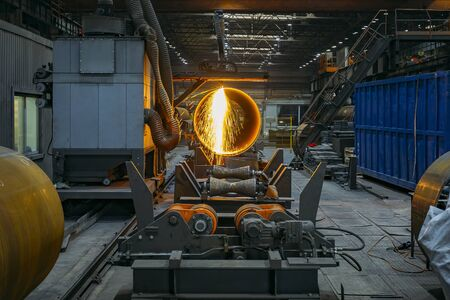Plasma cutting machine with CNC cutting steel pipe with sparks.