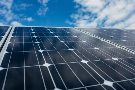 Solar panels on blue cloudy sky background.