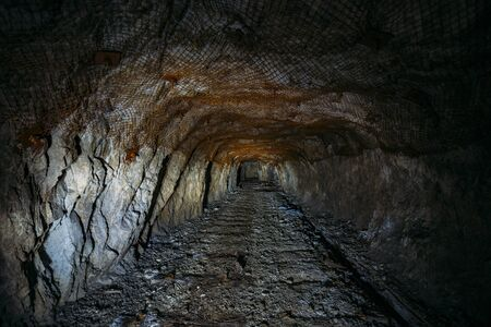 Dark dirty abandoned uranium mine with rusty remnants of railway. 写真素材