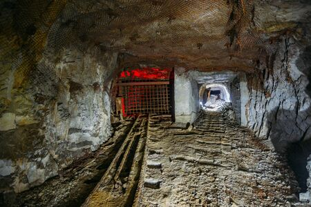 Dark dirty abandoned uranium mine with rusty remnants of railway.