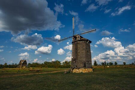 Wooden windmill on rural landscape in sunny summer day. Stok Fotoğraf