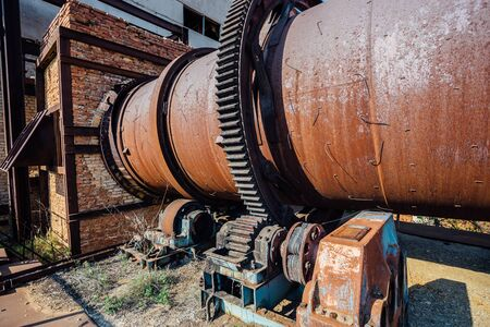 Old rusty rotating kiln in cement manufacturing plant