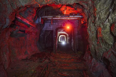 Dark dirty abandoned uranium mine with rusty remnants of railway color illuminated. Stok Fotoğraf - 130126820