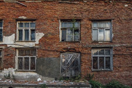 Old grungy wall of red brick with broken windows and wooden door.