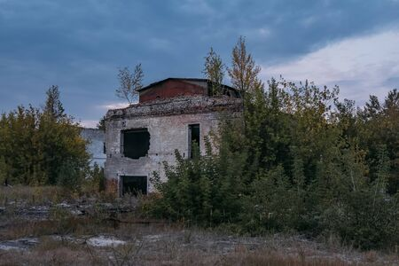 Ruined overgrown abandoned industrial building in evening. Stok Fotoğraf - 130126825