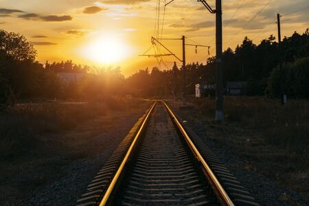 Empty railway track in sunny summer sunset.