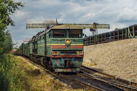Old green diesel locomotive moving cargo train.