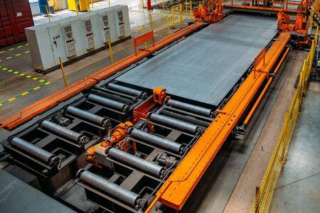 Steel sheet moving on roller conveyor in metalworking workshop.