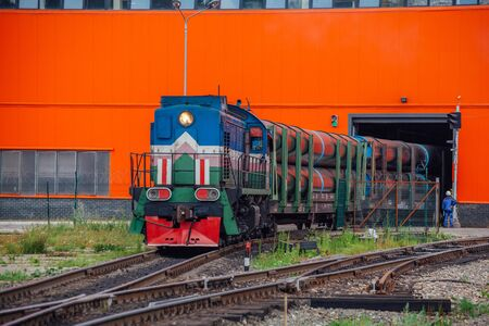 Freight train with new manufactured pipes exits from warehouse.