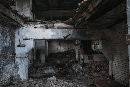 Old abandoned broken ruined industrial building interior.