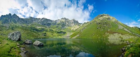 Panorama of clear calm mountain lake in summer day, highland lake Mzy, Abkhazia