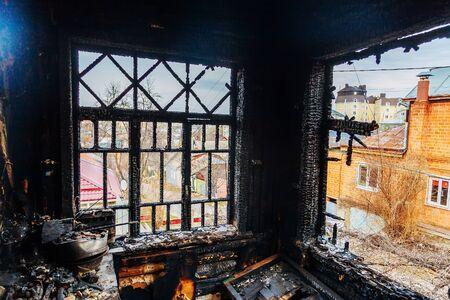 Burnt house interior. Burned kitchen, remains of furniture in black soot. Stok Fotoğraf