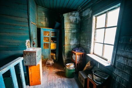 Dark and shabby messy room in poor apartment of old emergency abandoned wooden house, poverty concept. Stok Fotoğraf