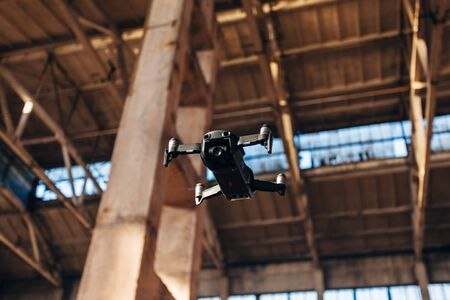 Quad-copter drone with camera flying inside industrial building.