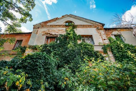 Old abandoned overgrown ruined house in Voronezh.