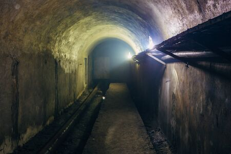 Vaulted underground tunnel  with electrical cables and rusty heating main pipeline. Фото со стока